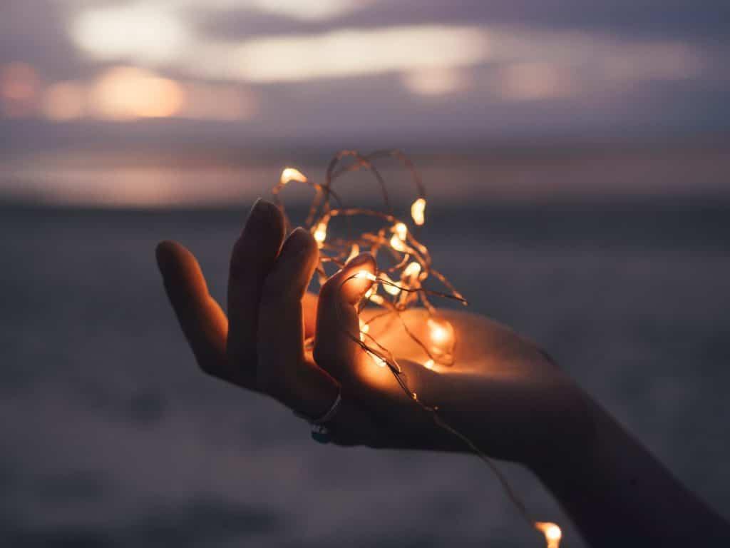 Mão segurando luzes com praia ao fundo