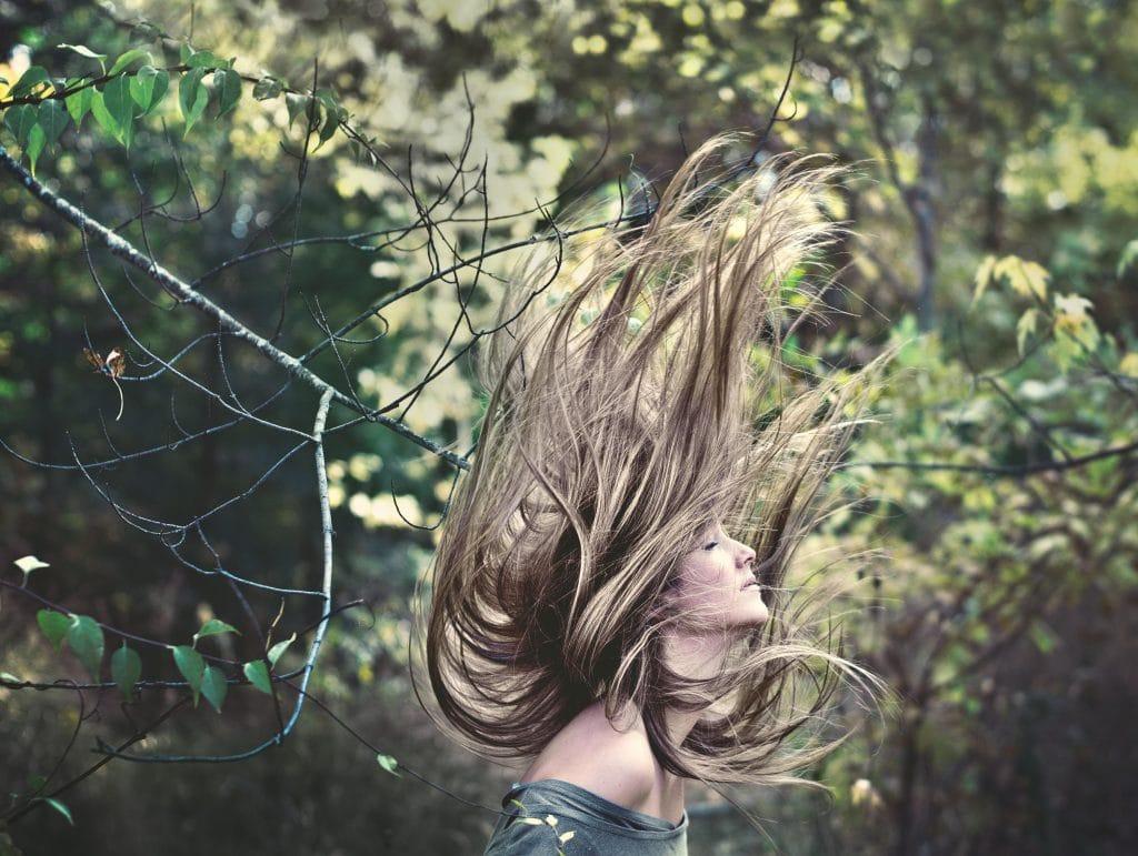 Mulher com cabelos para o alto de olhos fechados com fundo de floresta