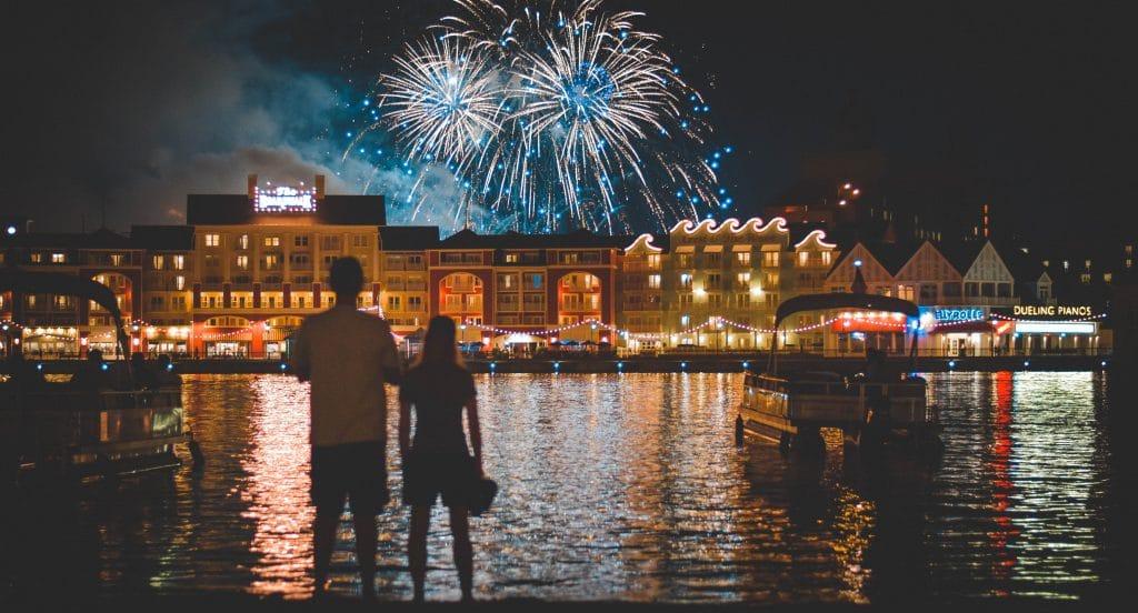 Casal de costas em frente a um rio, admirando os fogos de artifício sendo estourados no céu noturno.