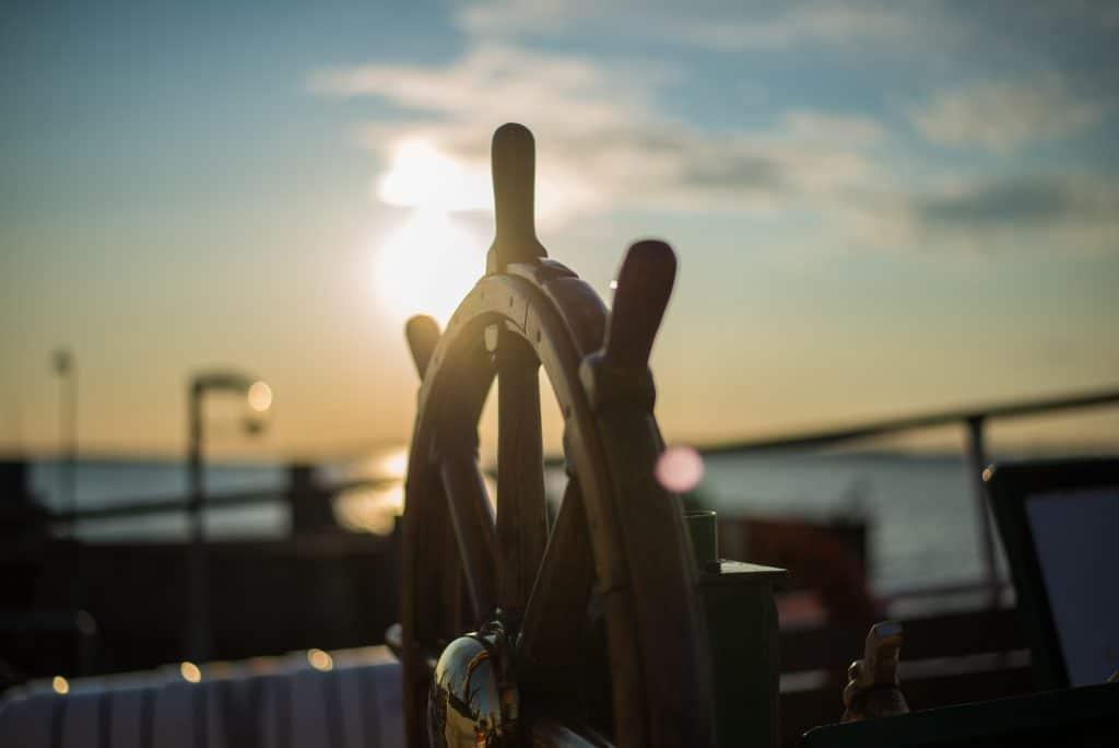 Timão de um navio em alto mar sob o dia ensolarado.