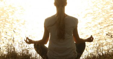 Mulher sentada de costas meditando em beira de riacho
