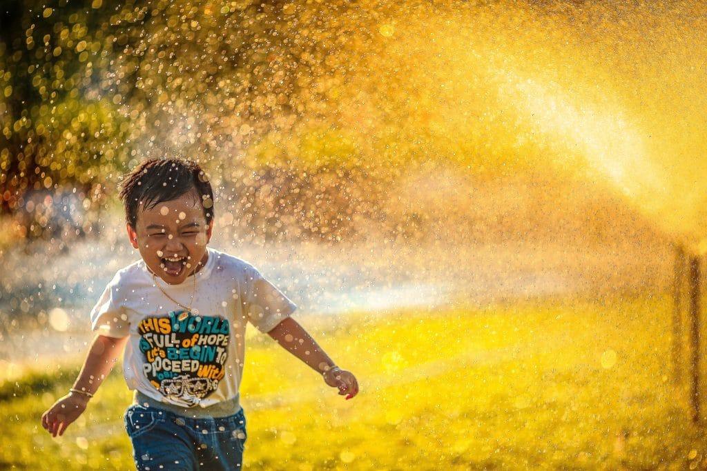 Menino correndo feliz entre esguicho de água