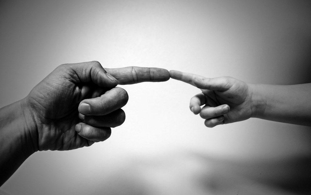 Foto em preto e branco de um dedo de criança tocando um dedo de um adulto.