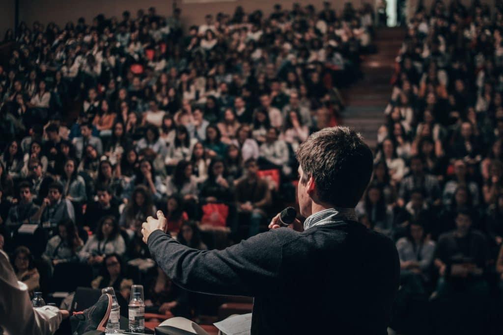 Homem de costas discursando com um microfone para várias pessoas em uma arquibancada.