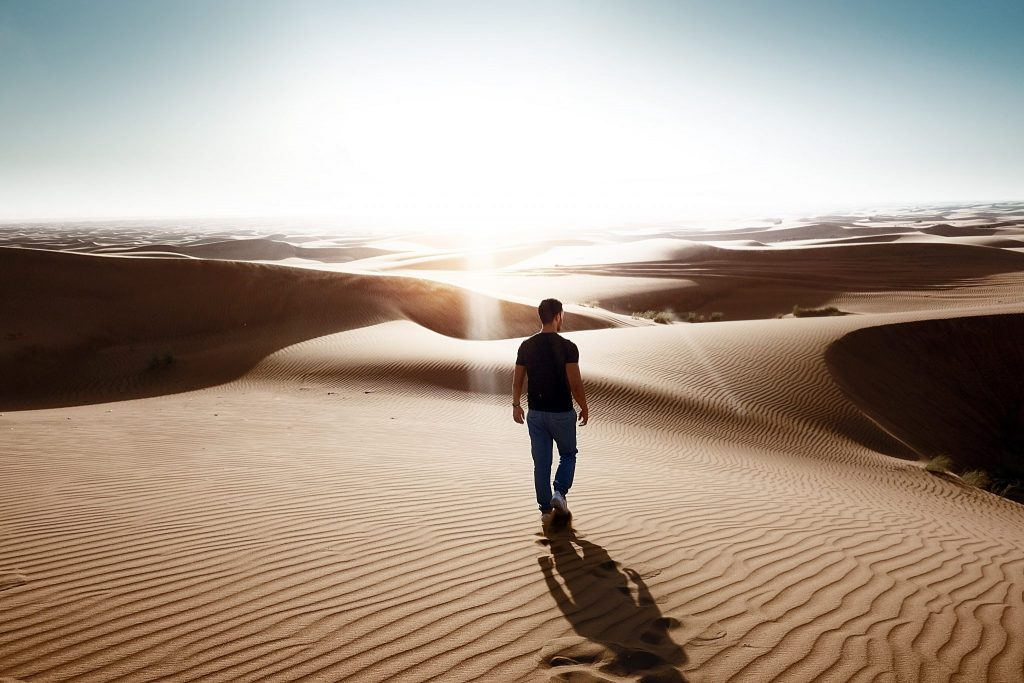 Homem de costas caminhando em deserto de areia