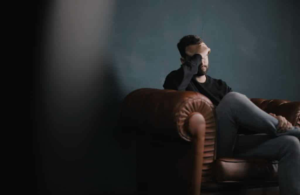 Homem sentado em sofá, com as pernas cruzadas e a mão sobre o rosto, aparentando estar estressado e infeliz.