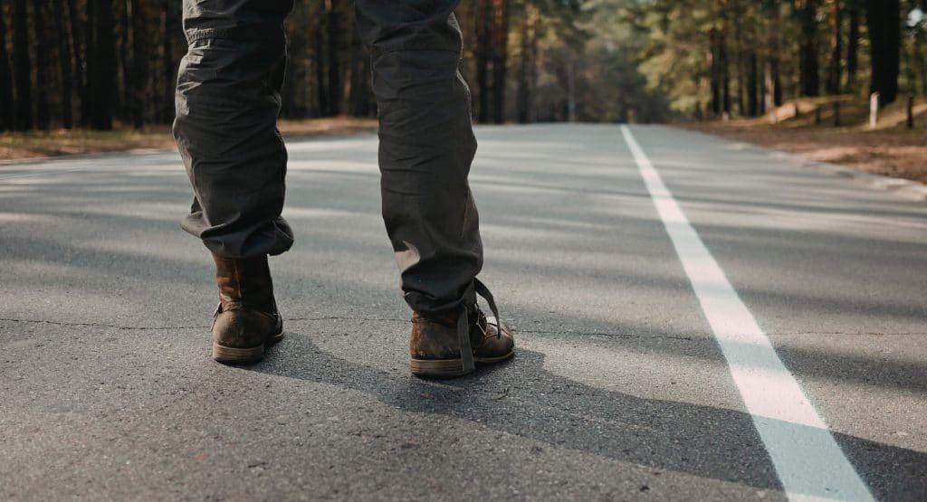 Homem parado no começo de uma estrada, de costas, representando o começo de uma nova jornada.