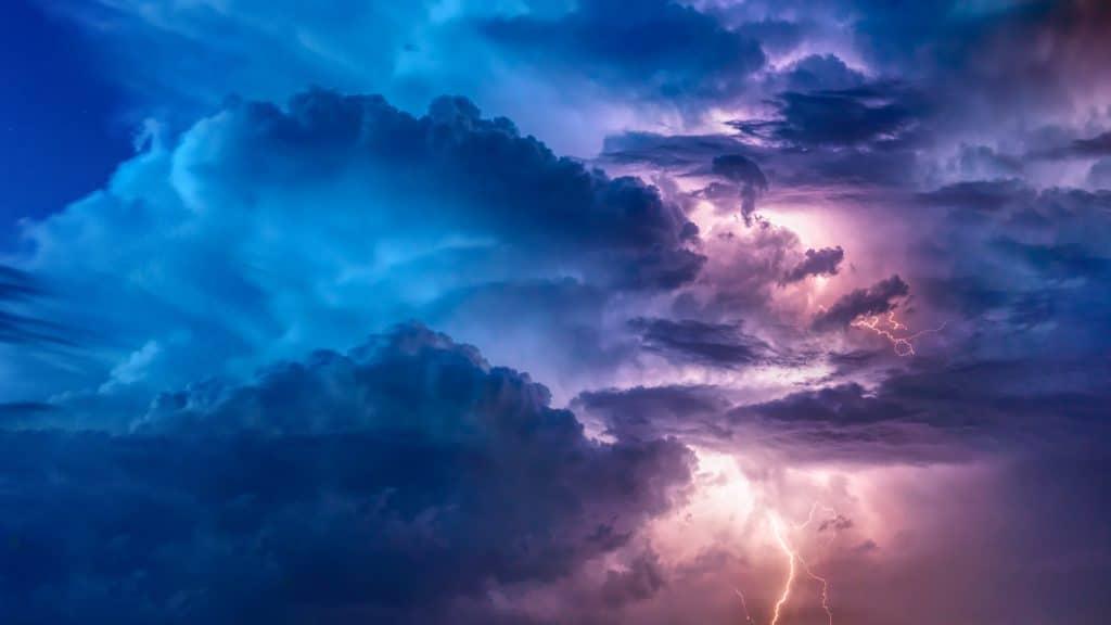 Relâmpago visto no céu, no começo da noite, repleto por nuvens.