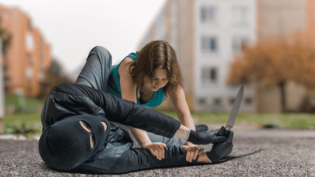 Mulher lutando contra um ladrão armado com uma faca