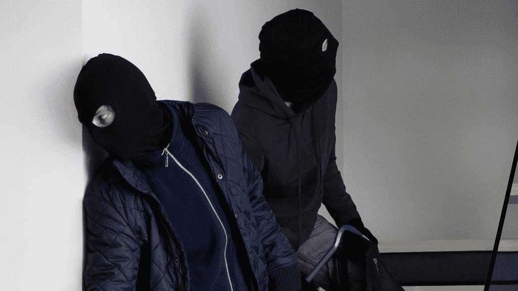 Dois ladrões fugindo de uma casa