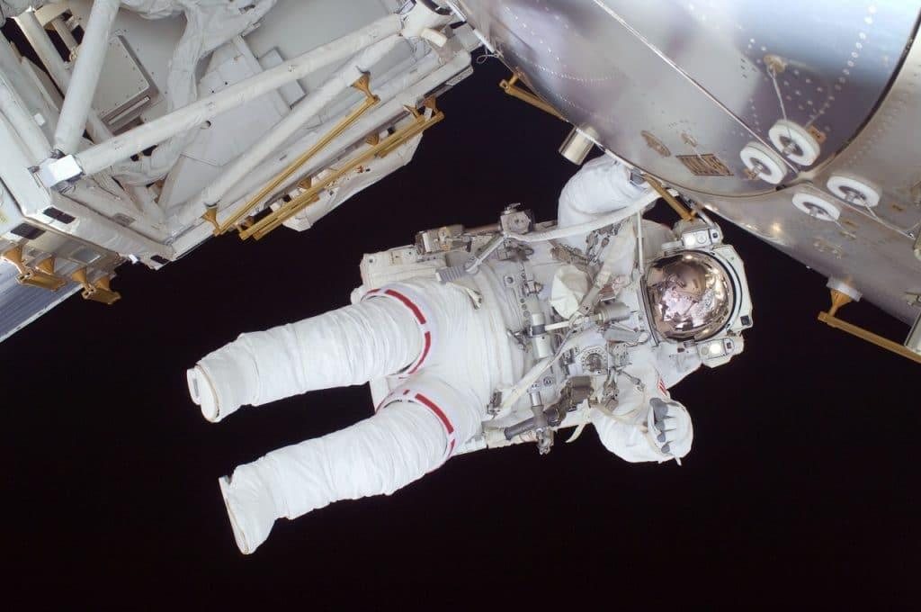 Astronauta em seu uniforme, no espaço, apoiado no exterior de sua nave. Foto tirada de baixo para cima.