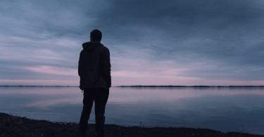 Homem em pé de costas com rio e céu nublado ao fundo