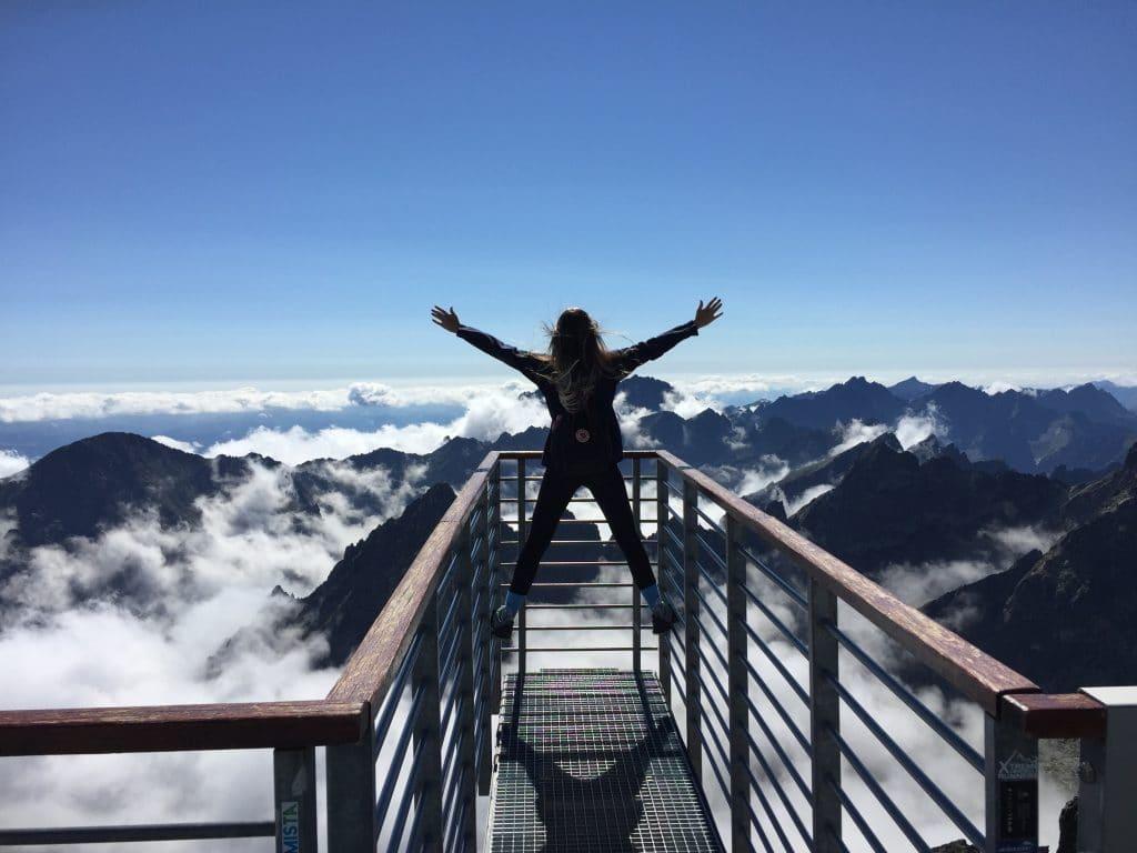 Mulher de braços abertos em ponte com montanhas e céu azul ao fundo