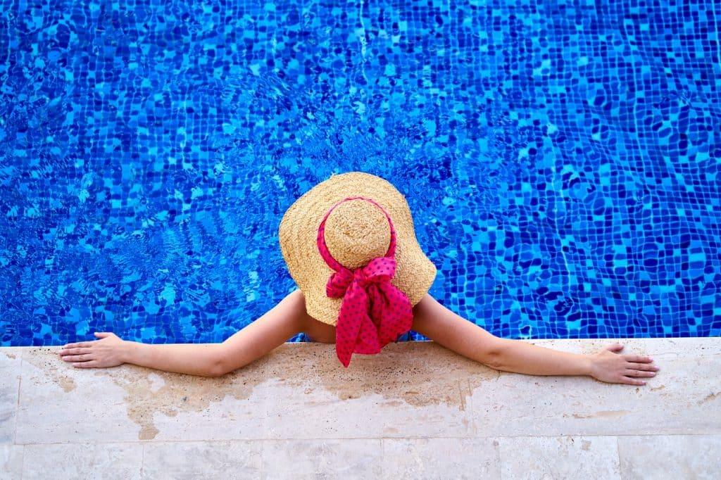 Mulher de costas com chapéu aproveitando a piscina.