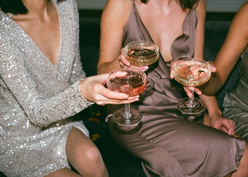 Três mulheres segurando taças de bebidas comemorando