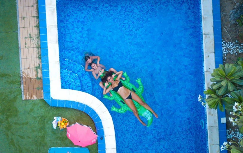 Mulher e duas crianças curtindo piscina.