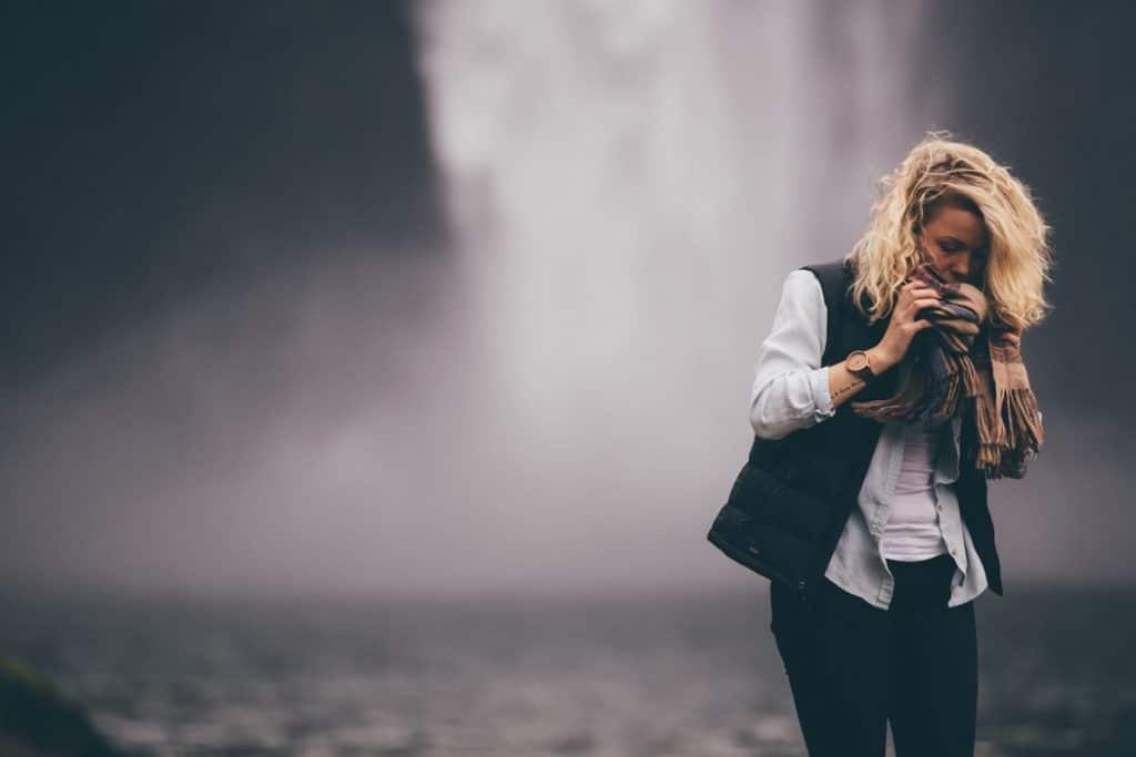 Mulher segurando echarpe próxima ao rosto com a intenção de cobri-lo. Atrás dela, vemos uma cachoeira.