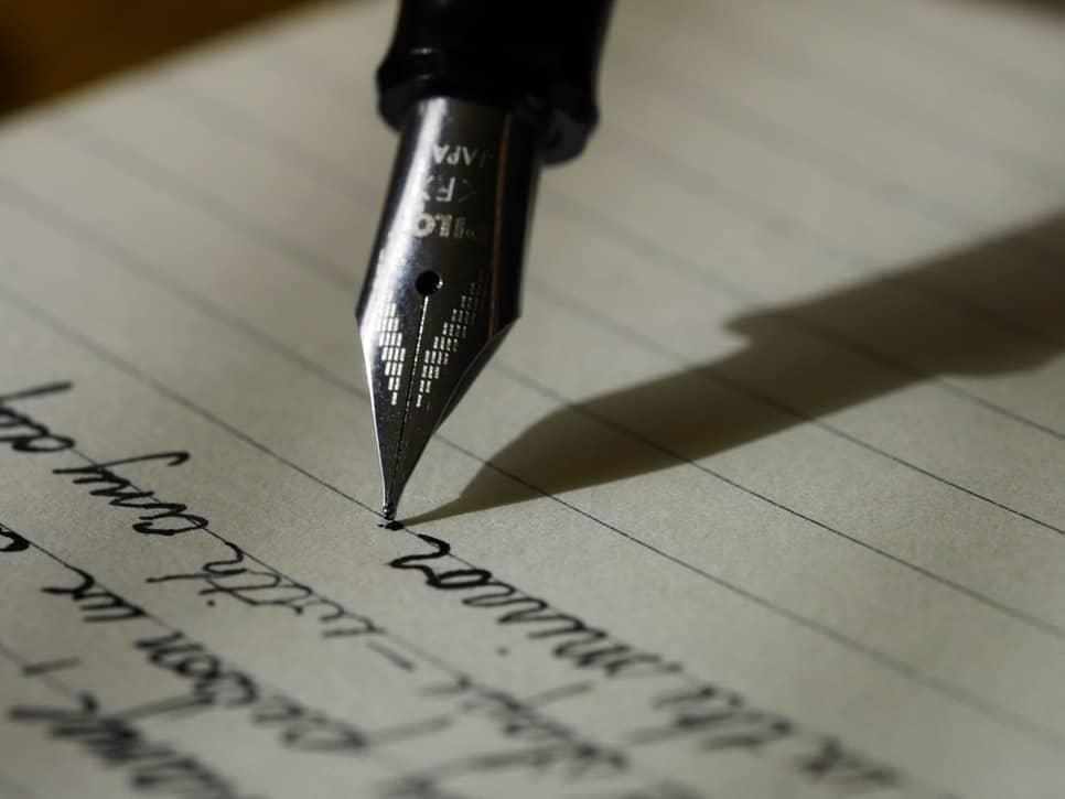 Imagem ampliada de uma caneta-tinteiro escrevendo sobre papel pautado.