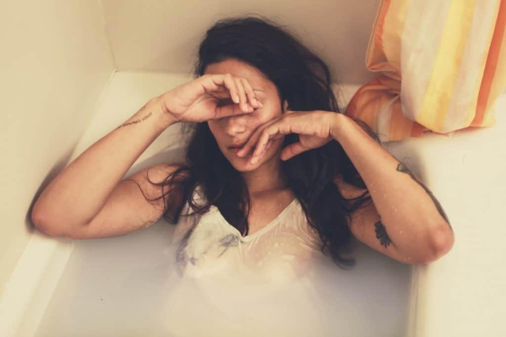 Mulher deita em banheira cheia, com um vestido branco.