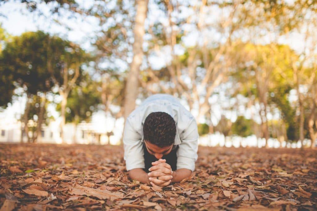 Homem ajoelhado em campo cheio de folhas secas. Seus cotovelos também estão apoiados no chão, e suas mãos estão entrelaçadas em frente. Sua cabeça está baixa.