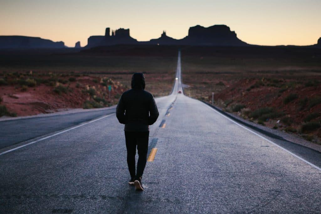 Homem de costas, de calça e capuz, andando sozinho no meio de uma estrada, no fim da tarde.