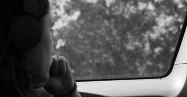 Foto em preto e branco de mulher jovem olhando pela janela do carro. Fora vemos árvores e mata fechada. A mulher apoia sua boca na mão esquerda, de forma pensativa.