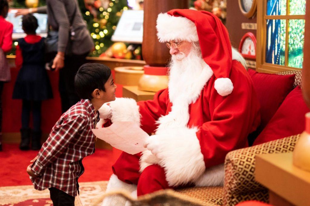 Menino pequeno em frente de um homem vestido como Papai Noel, que segura uma cartinha enquanto olha para a criança.