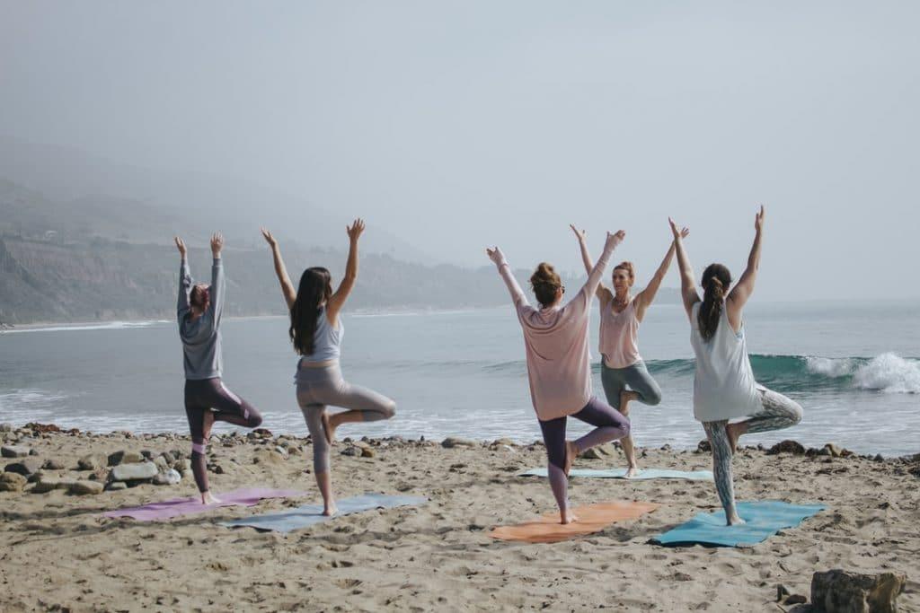 Grupo de mulheres praticando Yoga na praia, em frente ao mar.