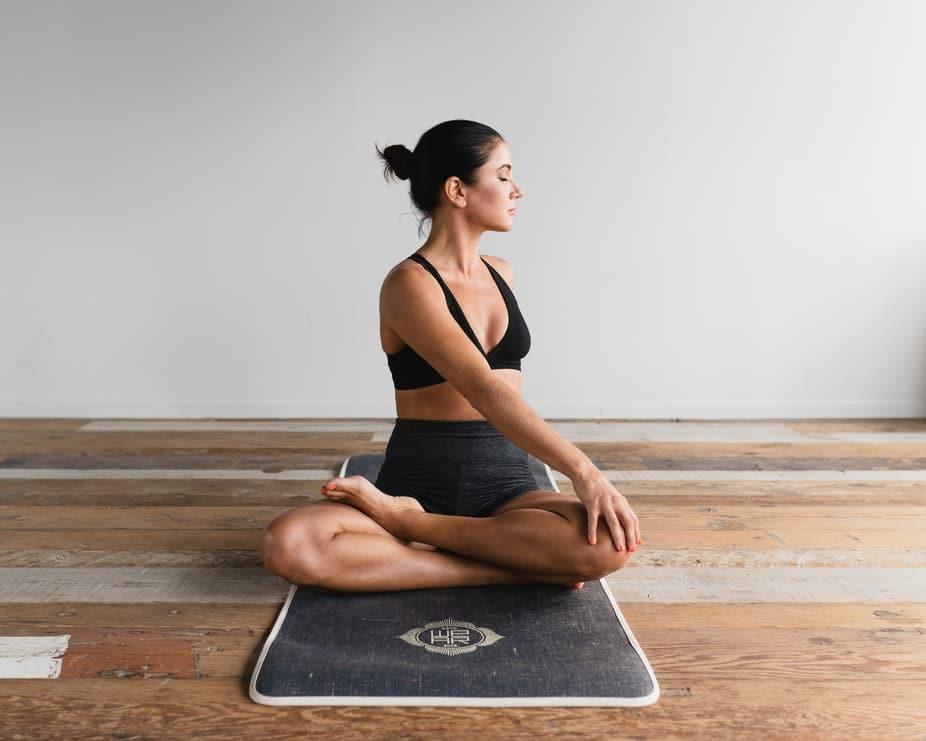 Mulher calma de olhos fechados praticando Yoga dentro de casa, sobre um tapete cinza em um chão de madeira.