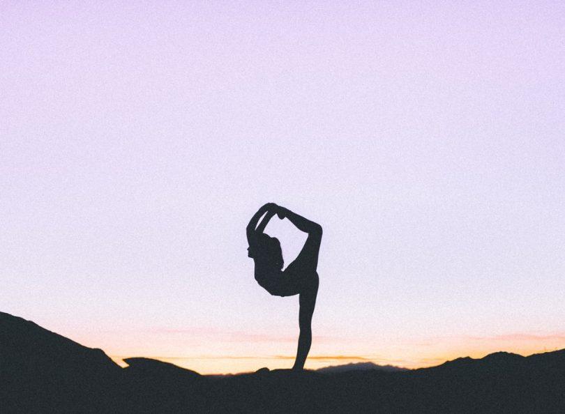 Silhueta de mulher praticando yoga sobre céu arroxeado.