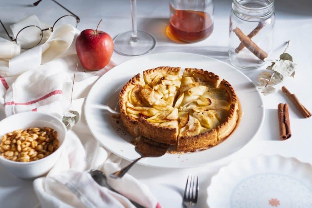 Torta de maçã em prato branco, com cortador de bolo embaixo de uma fatia. Ao redor, na mesa, um pote com paus de cnaela, um pote com amendoins , uma maçã, talheres e mel.