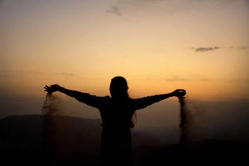 Silhueta de pessoa soltando areia pelas mãos durante o nascer do sol.