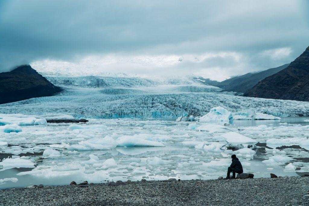 Homem sentado na beira de um lago glacial.