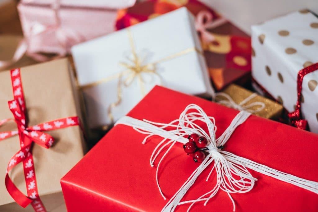 Presentes de Natal embrulhados em papéis de presente de cores diversas como vermelho, branco, bege e rosa.