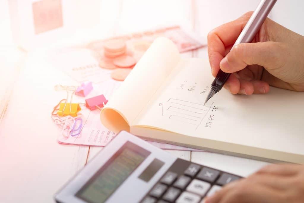 Mão com caneta e calculadora fazendo contas