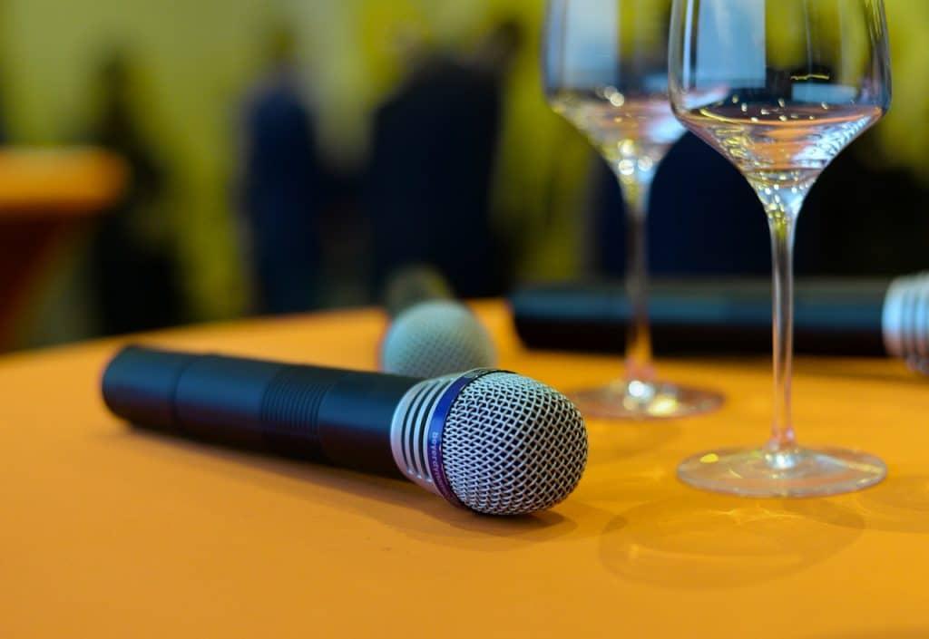 Microfones sem fio dispostos em uma mesa redonda, ao lado de taças de vidro.