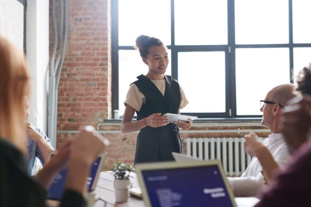 Menina discursando com um tablet em mãos durante uma reunião em ambiente de trabalho.