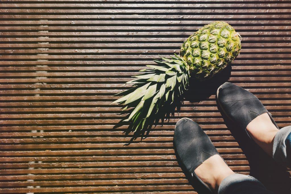 Pés ao lado de abacaxi.
