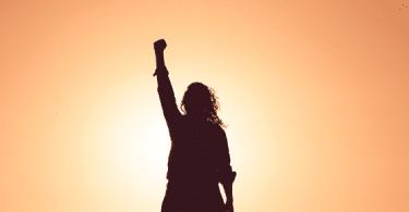 Silhueta de uma mulher em pé, com um braço estendido sobre a cabeça com o punho fechado, sob o pôr do sol.