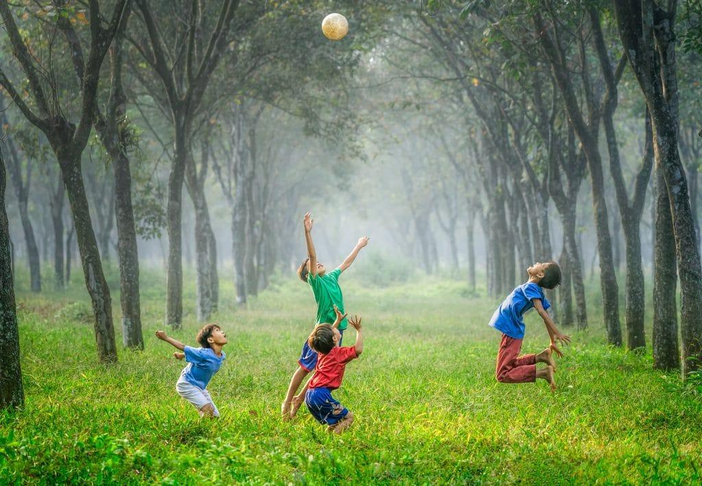 Meninos felizes jogando bola em gramado