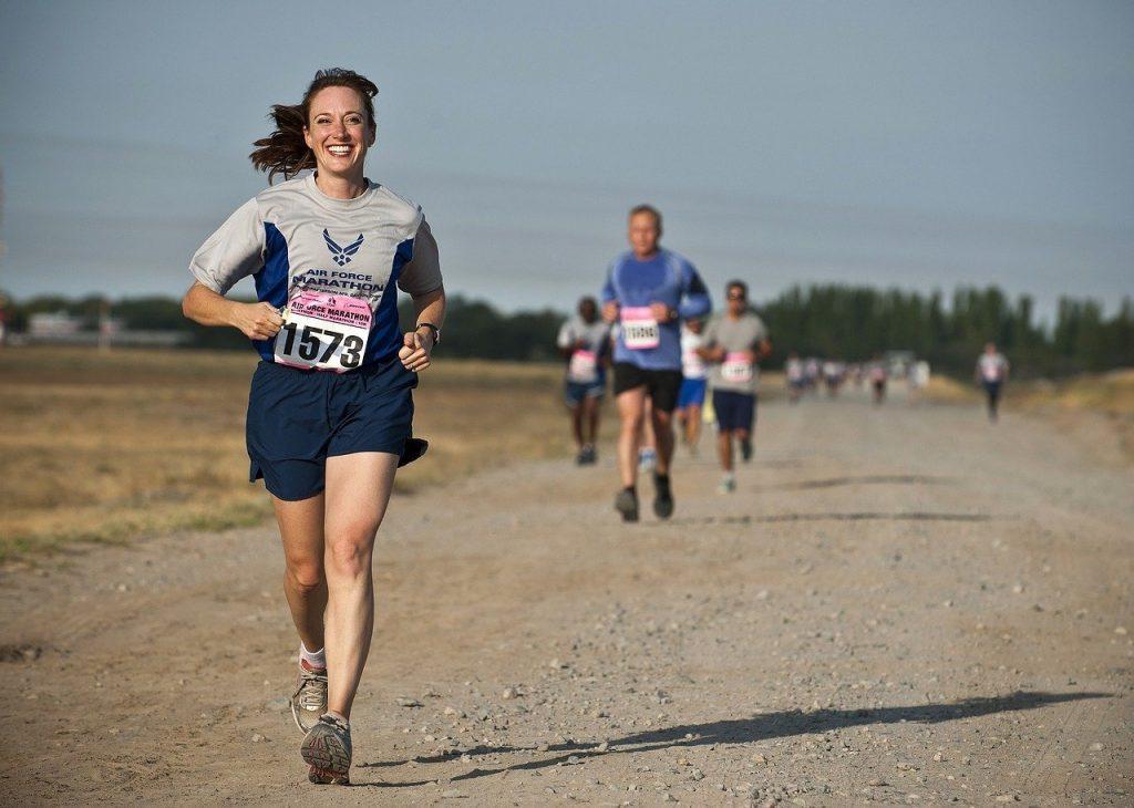 Mulher em uma competição de corrida, correndo com um sorriso no rosto.