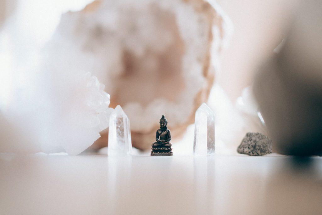 Cristais e Buda em foco com pedras maiores ao fundo