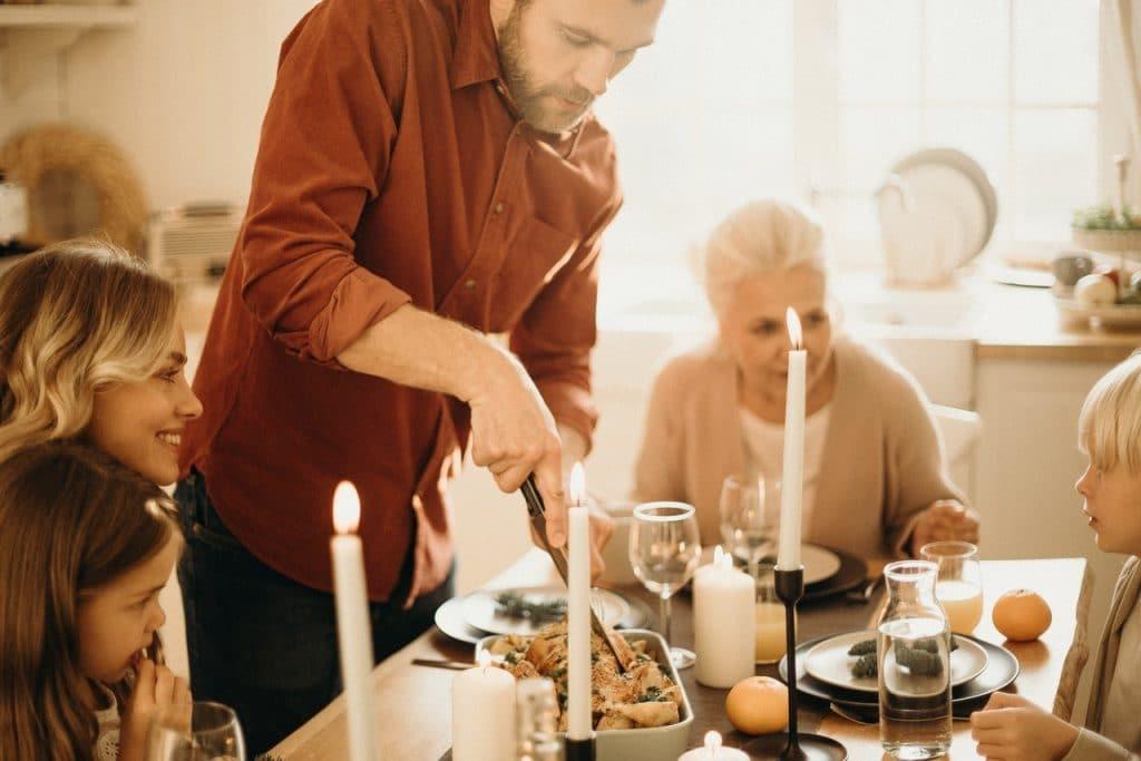 Homem servindo família em ceia de Natal.