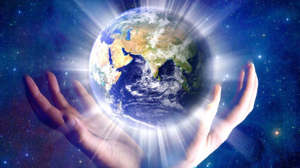 Mãos segurando um novo planeta Terra, que brilha sobre um fundo de galáxia.