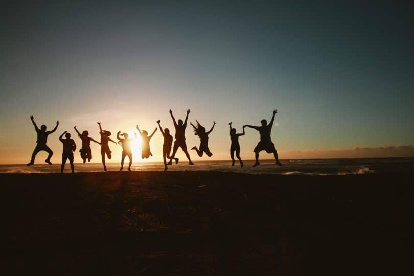 Silhueta de pessoas pulando em praia com pôr-do-sol ao fundo