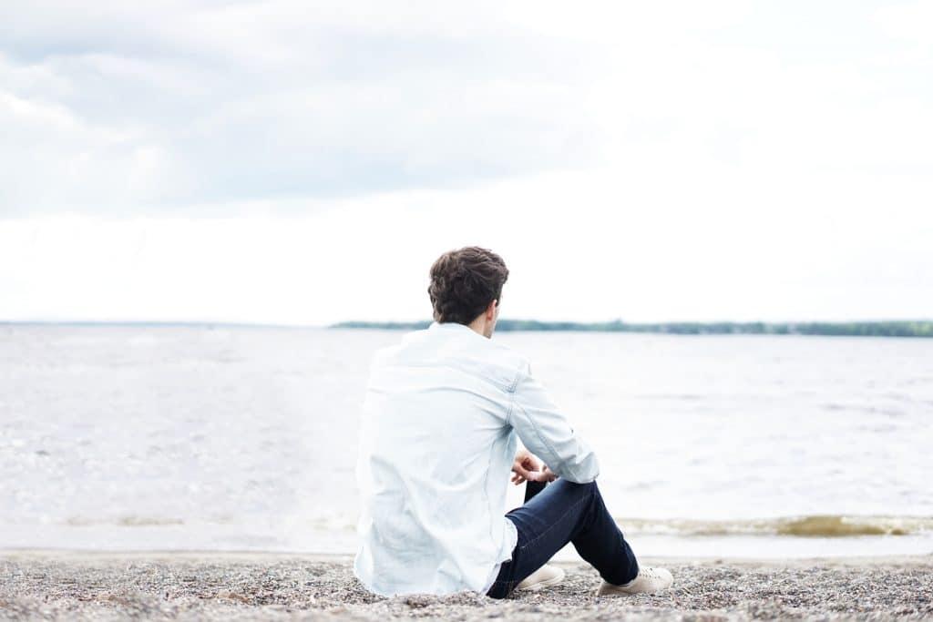 Homem de costas, vestindo uma camisa de manga longa e calça jeans, sentado na areia da praia, em frente ao mar.