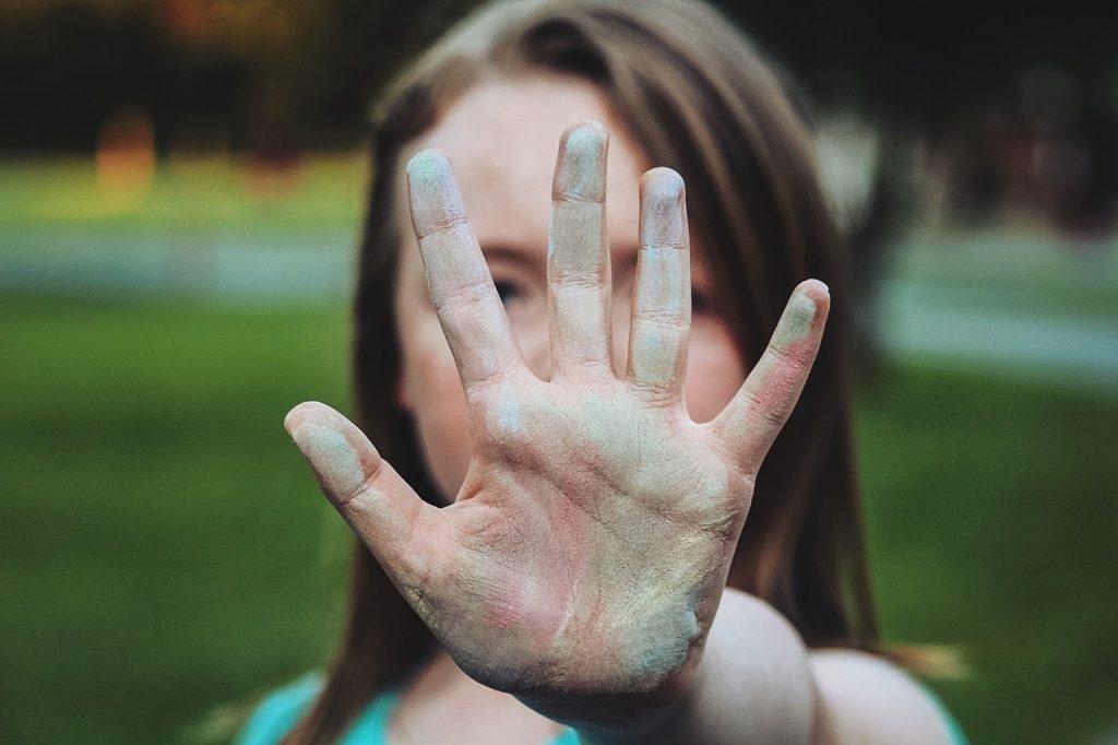 """Mulher com a palma da mão estendida na altura do rosto, em sinal de """"pare""""."""