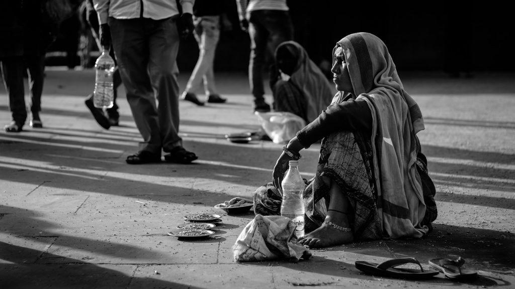 Foto em preto e branco de uma moradora de rua sentada no chão enquanto outras pessoas caminham.