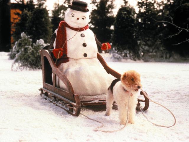 """Cena do filme """"Uma Noite Mágica"""", na qual o boneco de neve é carregado por um cachorro."""