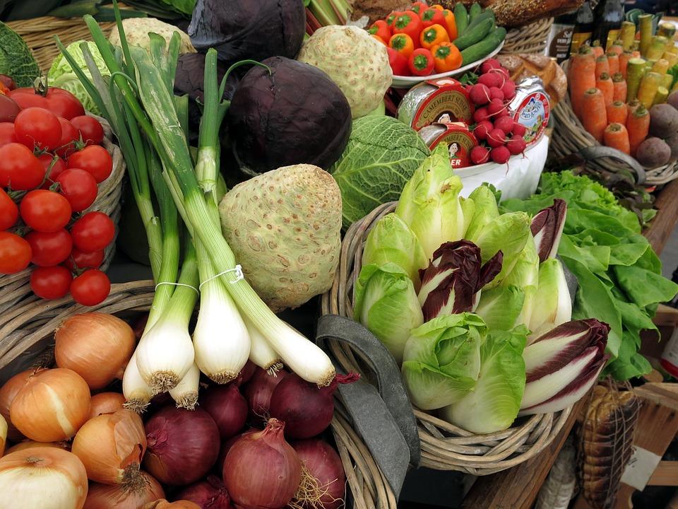 Uma banca com muitos vegetais expostos, como cebolas, cebolas roxas, tomates, alhos-porós, repolhos, cenouras e muitos outros.